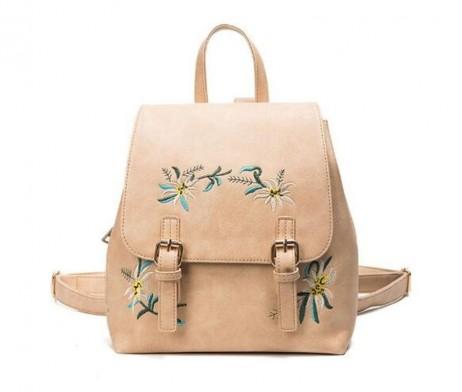 Vyšívaný kožený ruksak v bežovej farbe. Žena miluje kvety bez ohľadu na jej vek